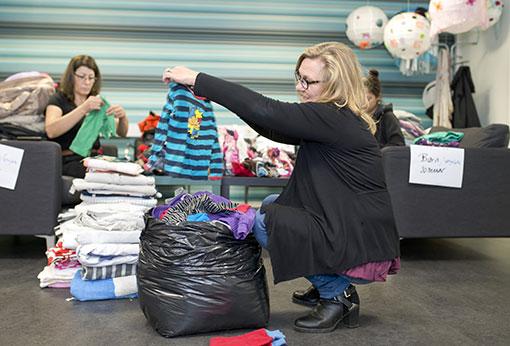 Städaren Kadega Abdallah packar ner i säckar och säljchefen Eira Järvi viker kläder.