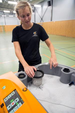 Städaren och robotoperatören Elin Antonsson visar vattentanken och ett de tre reningsfiltren.
