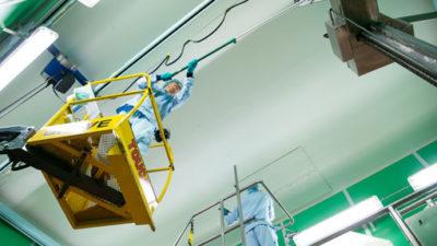 Luis Jara, i skyliften, och Sandeep Grewal moppar tak, rör och väggar. Foto: Anders G Warne